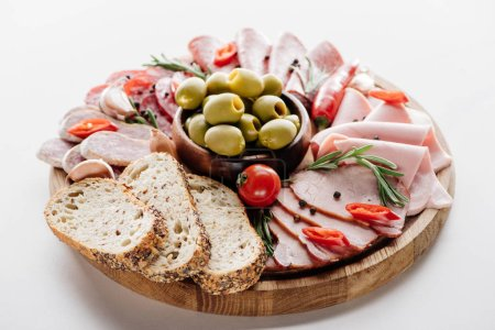 Photo for Round cutting board with delicious salami, ham, olives in bowl, bread, herbs and vegetables on white table - Royalty Free Image