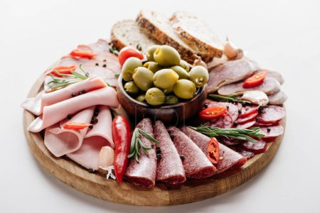round cutting board with olives in bowls, delicious salami, ham, sausages bread and vegetables on brown wrapping paper