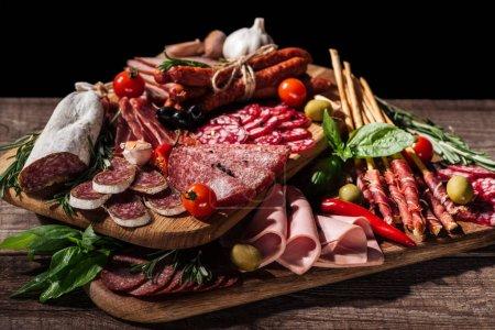 Photo pour Planches à découper avec délicieux salami, saucisses fumées, jambon et légumes sur table rustique en bois - image libre de droit