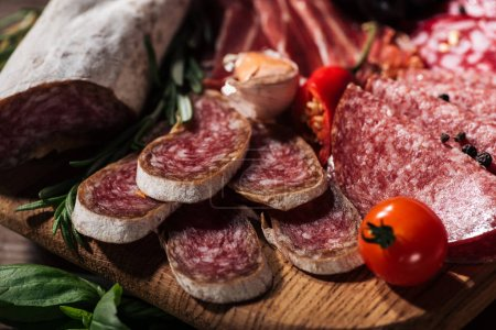 close up view of sliced salami with vegetables on wooden cutting board