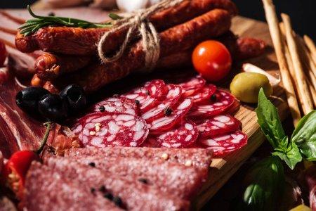 Photo pour Vue rapprochée de délicieuses saucisses fumées et de salami tranché aux légumes sur planche à découper en bois - image libre de droit
