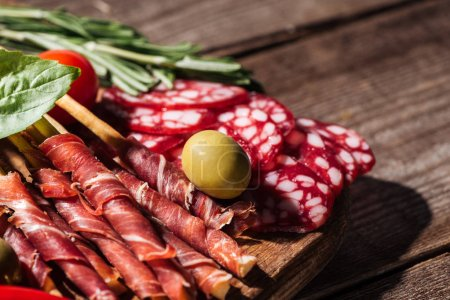 Photo for Close up view of cutting board with delicious sliced salami, prosciutto and herbs on wooden rustic table - Royalty Free Image