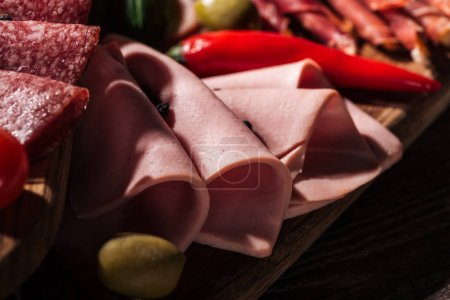 close up view of wooden cutting board with tasty sliced ham and vegetables
