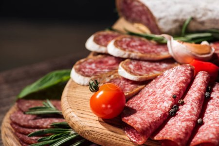close up view of wooden cutting boards with delicious sliced salami, herbs and vegetables