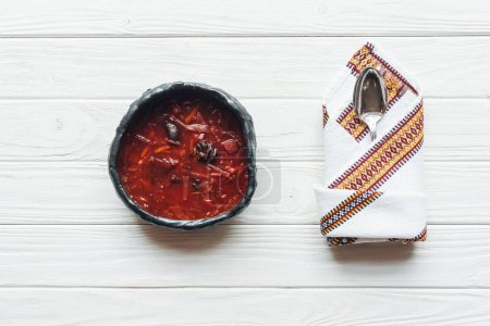 top view of traditional beetroot soup with spoon and embroidered towel on white wooden background