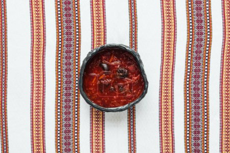 top view of traditional tasty beetroot soup with embroidered towel on background