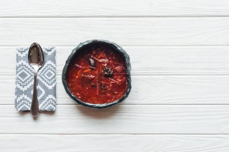 top view of traditional beetroot soup and spoon on white wooden background with copy space