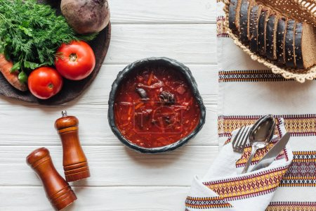top view of traditional beetroot soup with cutlery, ingredients and rye bread on white wooden background
