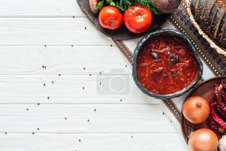 Photo pour Soupe de betterave traditionnelle avec ingrédients et piment sur fond blanc en bois avec espace de copie - image libre de droit