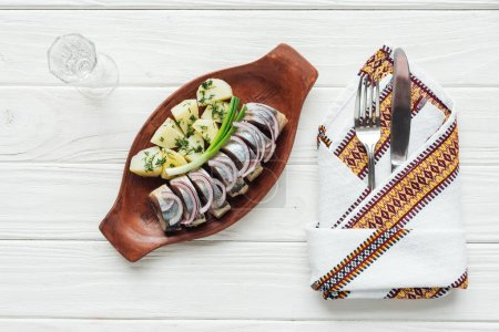 Photo for Marinated herring, potatoes and onions in earthenware plate with glass of vodka, cutlery and embroidered towel on white wooden background - Royalty Free Image