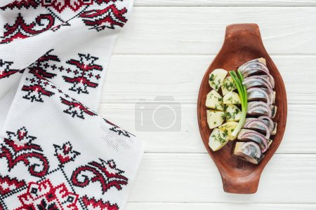 Photo for Top view of marinated herring with potatoes and onions in earthenware plate with embroidered towel on white wooden background - Royalty Free Image
