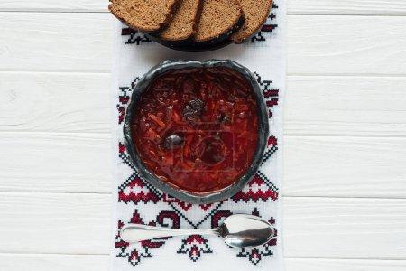 Photo pour Bol de soupe traditionnelle aux betteraves avec serviette brodée et pain de seigle sur fond de bois blanc - image libre de droit