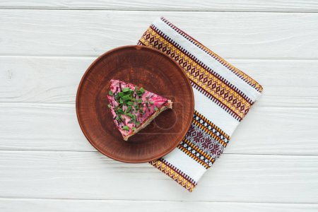 top view of tasty traditional russian salad on plate with embroidered towel on white wooden background