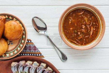 Photo pour Vue de dessus de soupe traditionnelle savoureuse de viande mélangée avec mini tartes et cuillère sur fond blanc en bois - image libre de droit