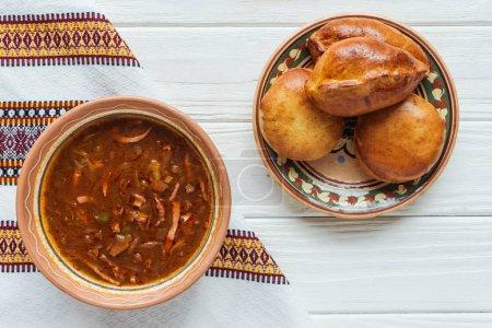Photo pour Délicieuse soupe traditionnelle de viande mélangée avec mini tartes et serviette brodée sur fond de bois blanc - image libre de droit