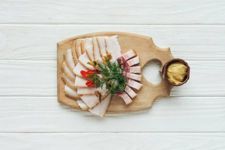 top view of traditional sliced smoked lard with mustard on cutting board with white wooden background