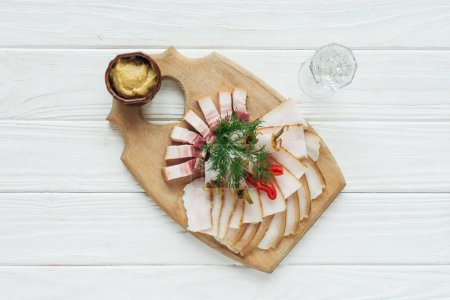 top view of traditional sliced smoked lard on cutting board with mustard and glass of vodka on white wooden background