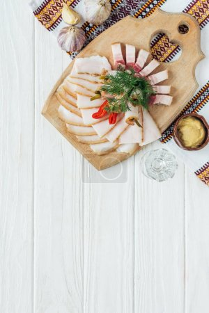 traditional sliced smoked lard on cutting board with mustard, embroidered towel and glass of vodka on white wooden background