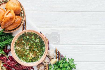 Photo pour Vue du dessus de la soupe de poisson traditionnelle avec oignon vert, serviette brodée, ingrédients et mini tartes sur fond de bois blanc - image libre de droit