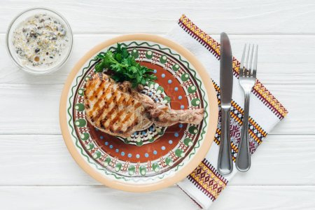 top view of rib eye meat steak on plate with parsley, cutlery and embroidered towel on white wooden background