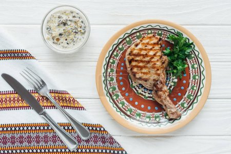 top view of rib eye meat steak on plate with parsley, sauce, embroidered towel and cutlery on white wooden background