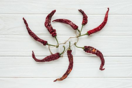 bundle of red chilli peppers on white wooden background