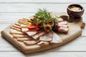 traditional tasty sliced smoked lard with dill, chilli pepper and mustard on cutting board with white wooden background