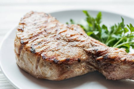 Photo for Close up of delicious rib eye meat steak on plate with parsley - Royalty Free Image