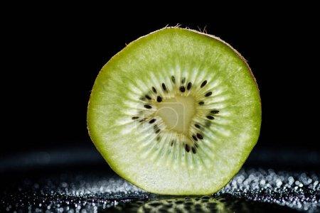 slice of kiwi fruit on black background