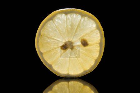 Photo for Slice of fresh ripe lemon isolated on black - Royalty Free Image
