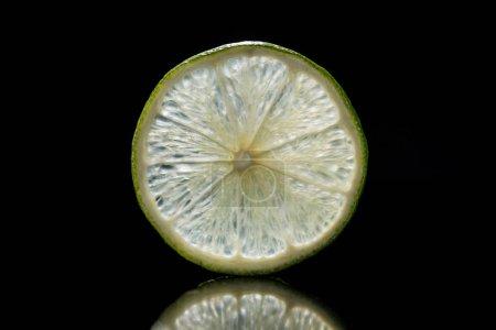 slice of fresh ripe lime isolated on black