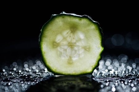slice of cucumber with bokeh on black background