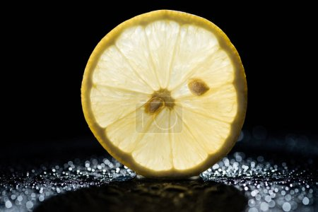 Photo for Slice of lemon on black background with water drops and backlit - Royalty Free Image
