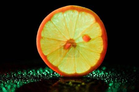 Photo pour Tranche de citron avec rétro-éclairé de néons sur fond noir - image libre de droit