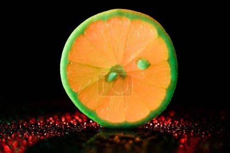 Photo pour Tranche de citron néon avec bokeh sur fond noir - image libre de droit