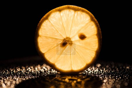 Photo for Slice of fresh lemon on black background with yellow backlit - Royalty Free Image