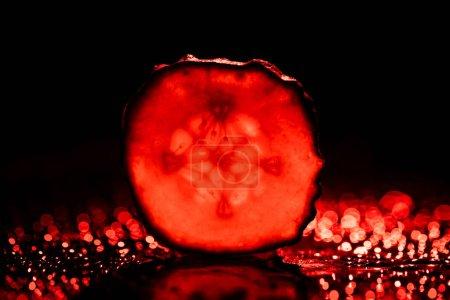 Foto de Rodaja de pepino con neón rojo luz sobre fondo negro - Imagen libre de derechos