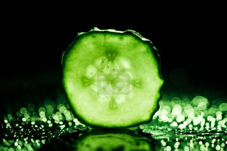 Photo for Slice of cucumber with green back light on black background - Royalty Free Image