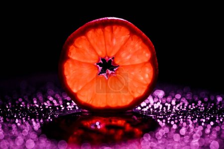 slice of grapefruit on black background with red backlit and bokeh