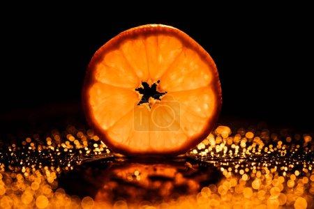 Photo pour Rondelle d'orange sur fond noir avec bokeh et rétro-éclairé - image libre de droit