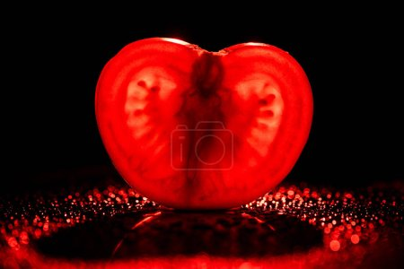 slice of fresh tomato with neon red backlit on black background