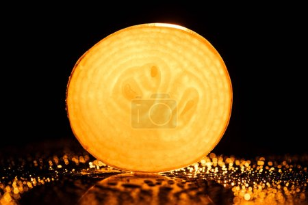 Photo pour Tranche d'oignon cru avec des gouttes d'eau et néon orange rétro-éclairage sur fond noir - image libre de droit
