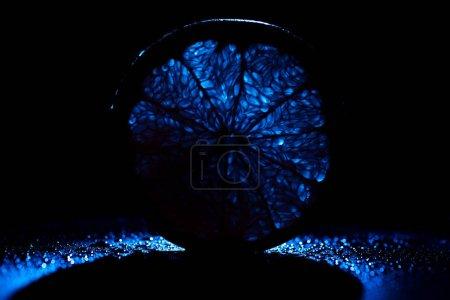 Photo pour Tranche d'orange avec rétroéclairage néon bleu sur fond noir - image libre de droit