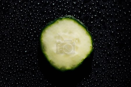 Photo for Slice of cucumber on black background with water drops - Royalty Free Image