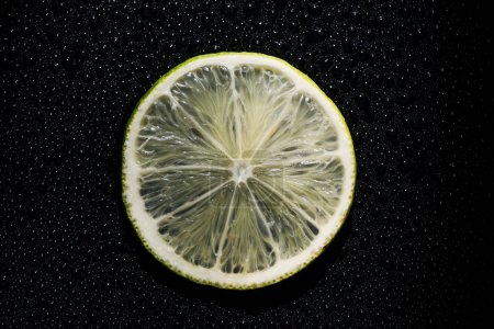 slice of fresh lime on black background with water drops