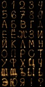close up view of light russian alphabet and numbers on black background