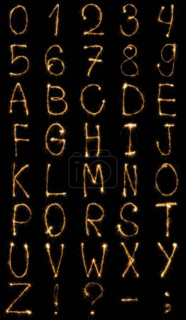 close up view of light english alphabet and numbers on black background