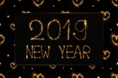 2019 new year light lettering and hearts light signs on black background