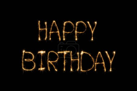 close up view of happy birthday light lettering on black backdrop