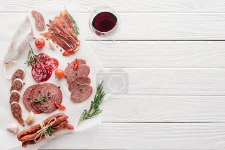 food composition with glass of red wine and assorted meat snacks on white wooden tabletop